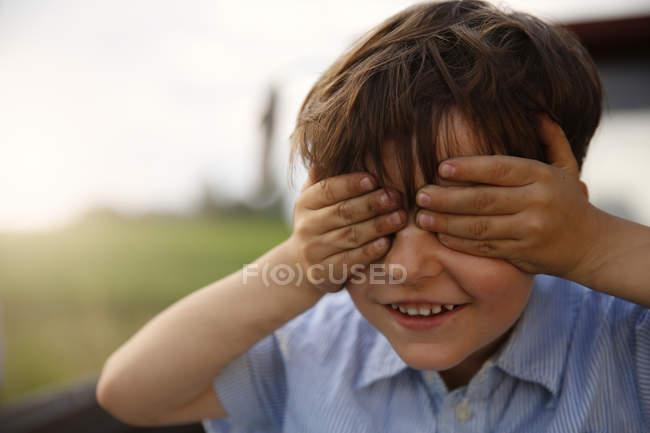 Retrato de menino sorridente cobrindo os olhos com as mãos — Fotografia de Stock