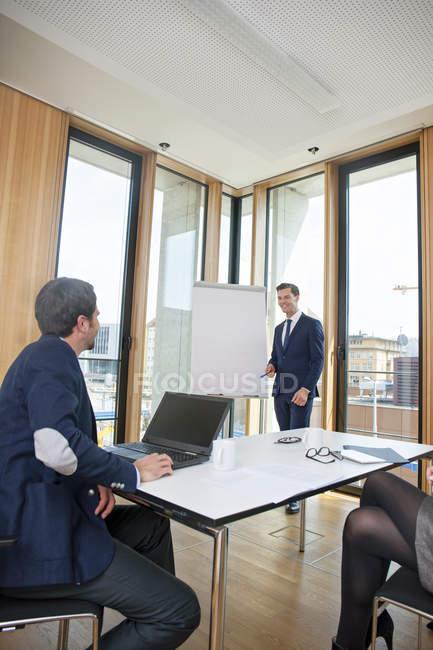 Homme d'affaires menant une présentation au tableau à feuilles mobiles — Photo de stock