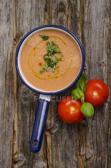 Saucepan of tomato sauce, tomatoes and basil leaves on wood — Stock Photo
