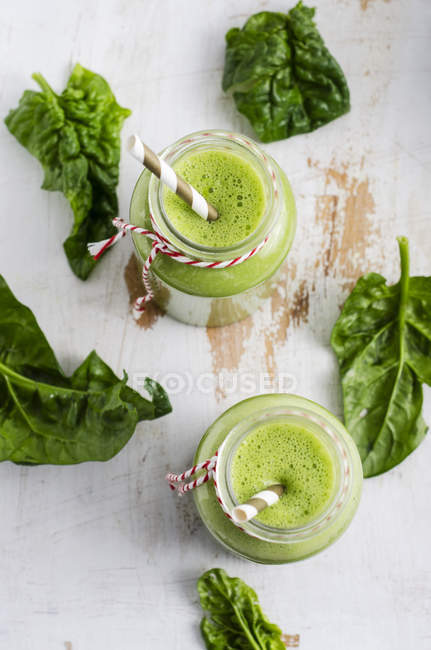Two glasses of spinach smoothie and spinach leaves on white wood — Stock Photo