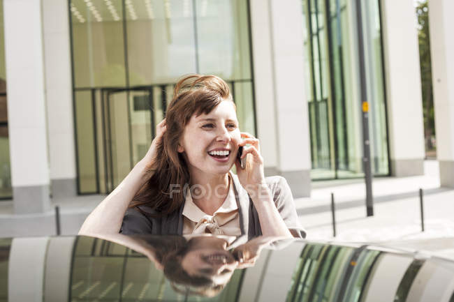 Smiling businesswoman telephoning with smartphone near car — Stock Photo
