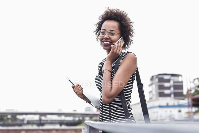 Mulher de negócios sorrindo telefonando com telefone celular na cidade — Fotografia de Stock