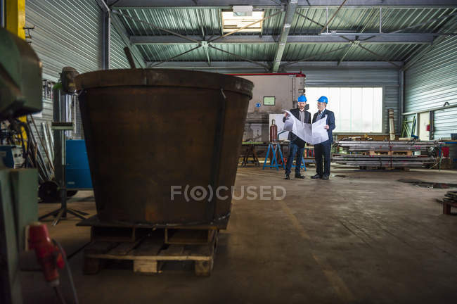 Ingenieure mit Plan in Werkstatt — Stockfoto