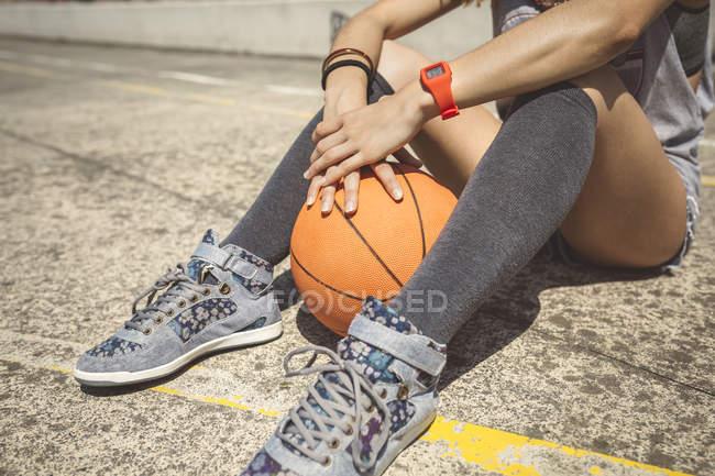 Jovem mulher sentada no chão do campo de baketball com bola entre as pernas — Fotografia de Stock