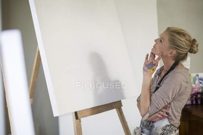 Mujer observando el lienzo antes de instalar en casa de arte studio - foto de stock