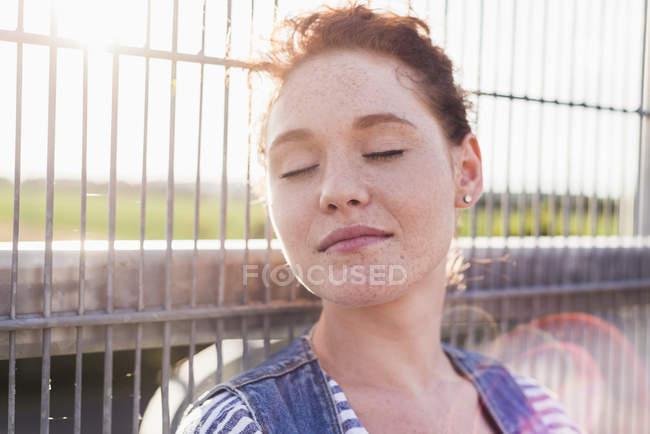 Молодая женщина с закрытыми глазами у забора — стоковое фото