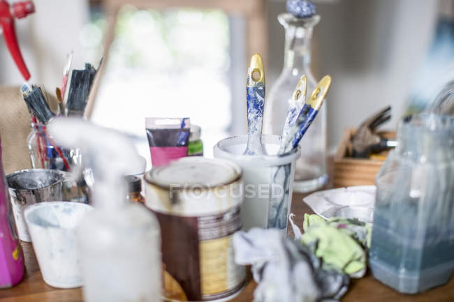 Different utensils, brushes and paints on table in workshop — Stock Photo