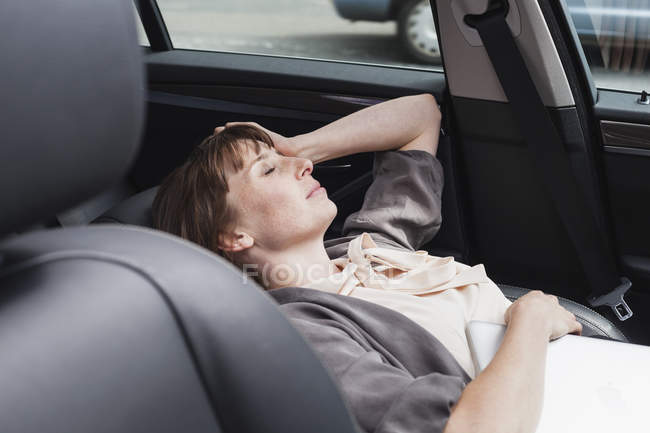 Tired businesswoman with eyes closed relaxing in car — Stock Photo
