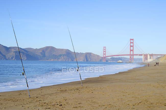 EUA, Califórnia, São Francisco, varas de pesca em Baker Beach e Golden Gate Bridge — Fotografia de Stock