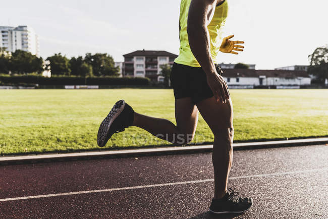 Cropped image of male athlete running on tartan track — Stock Photo