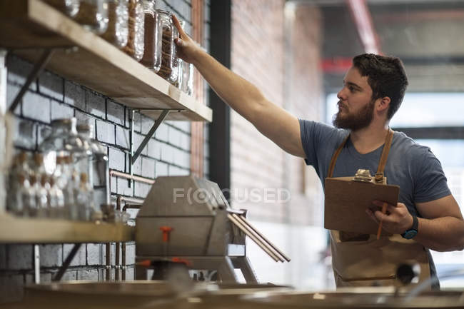 Caucasian man reaching out for a jar in distillery — Stock Photo