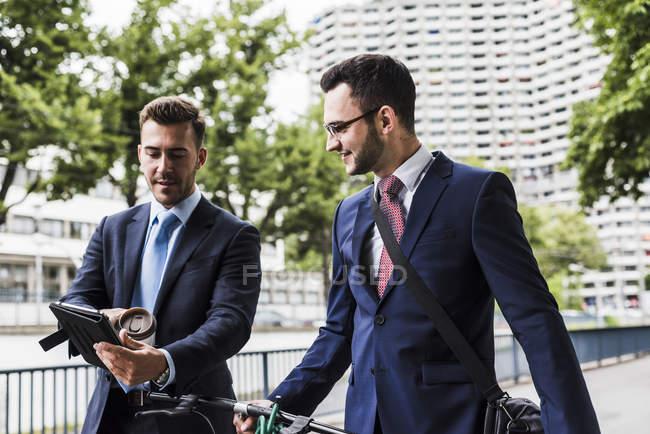 Бизнесмены, гуляющие на велосипеде по городу и разговаривающие — стоковое фото