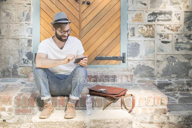 Man outdoors sitting on steps looking at cell phone — Stock Photo