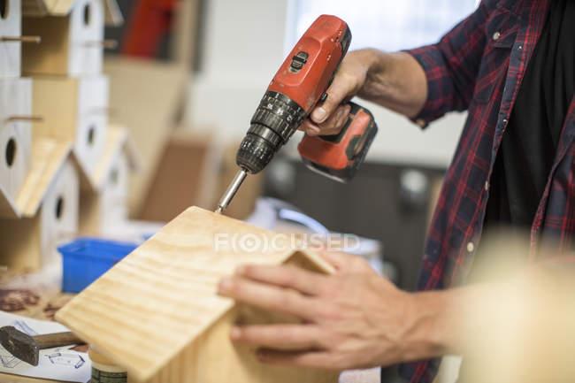 Обрезанное изображение человека, работающего с электрической дрелью на скворечнике в мастерской — стоковое фото
