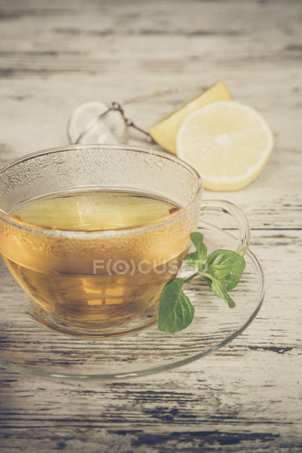 Fresh mint tea in glass cup over wooden surface — Stock Photo