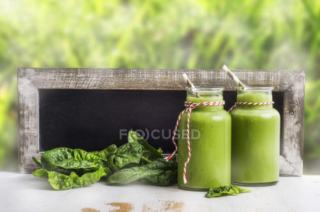 Two glasses of green spinach smoothie, spinach leaves and blackboard — Stock Photo