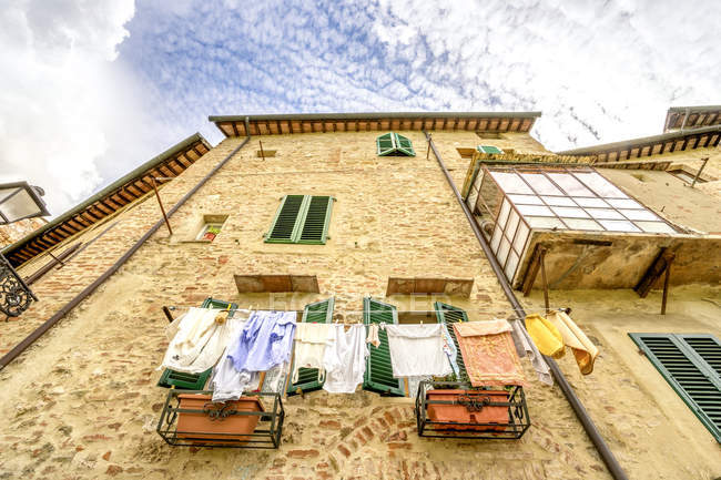 Italy, Tuscany, San Gimignano, view of house facade with hanging cloth — стоковое фото