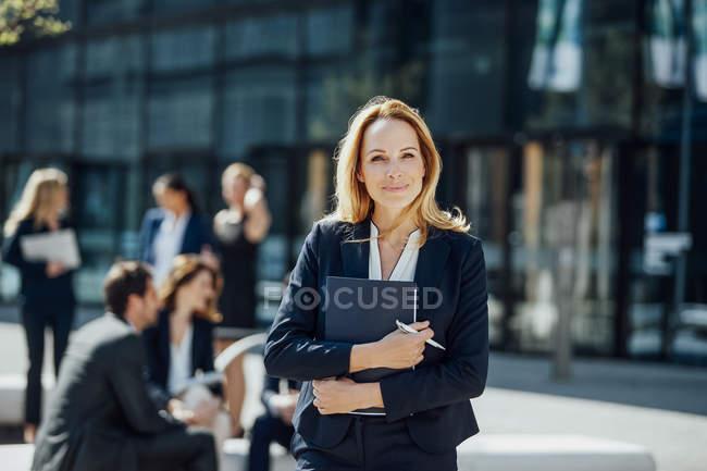 Portrait d'une femme d'affaires souriante devant un immeuble de bureaux — Photo de stock