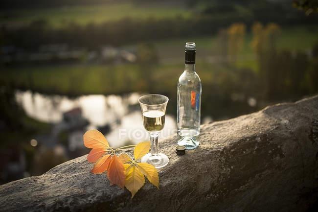 Garrafa de vinho branco e vidro em parapeito ao sol da noite — Fotografia de Stock