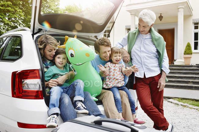 Famiglia seduta nel bagagliaio della macchina, prepararsi per il viaggio — Foto stock