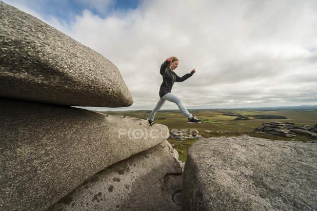 Vereinigtes Königreich, England, Kornwand, Bodmin Moor, grobe Tor, Felsformation, Mädchen springen — Stockfoto