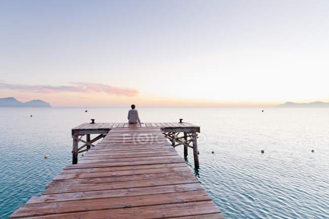 Испания, Балеарские острова, Майорка, мальчик-подросток, сидящий утром на причале — стоковое фото