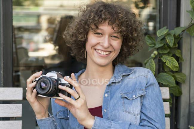Портрет улыбающейся молодой женщины со старой камерой, сидящей в кафе на тротуаре — стоковое фото