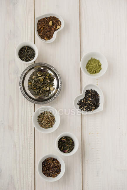 Closeup of bowls of various sorts of tea on white wooden table — Stock Photo