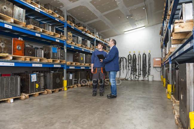 Deux hommes examinant des blocs de machines dans un entrepôt — Photo de stock