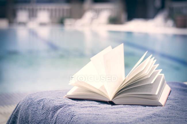 Открытая книга на полотенце у бассейна — стоковое фото