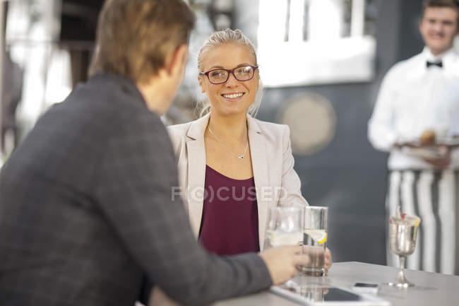Woman smiling at man at outdoor restaraunt — Stock Photo