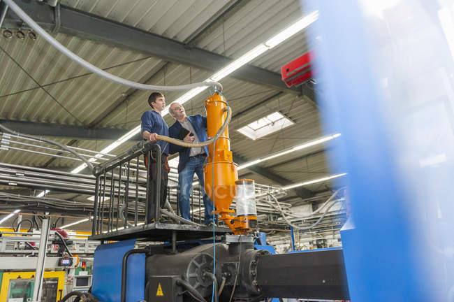 Менеджер и работник, работающий на заводе пластмасс — стоковое фото
