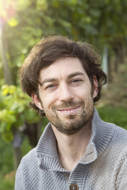 Porträt eines Winzers, der im Weinberg in die Kamera blickt — Stockfoto