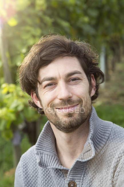 Портрет winegrower дивлячись на камеру в виноградник — стокове фото