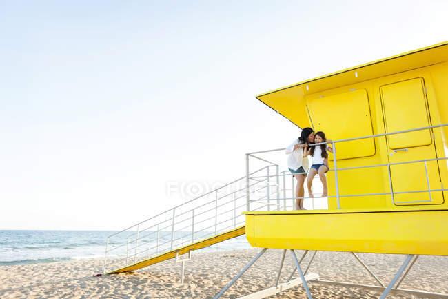 Матері цілуватися малою донькою жовтий рятувальник стенд — стокове фото