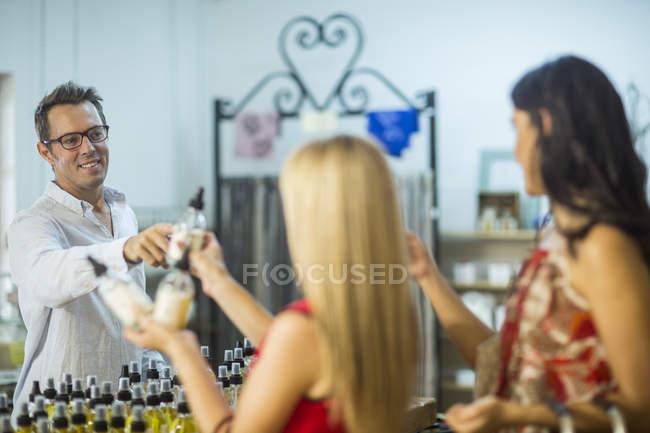 Мужчина, передающий духи женщине в магазине — стоковое фото