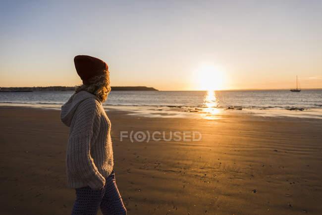 Adolescente caminhando na praia de areia ao pôr do sol — Fotografia de Stock