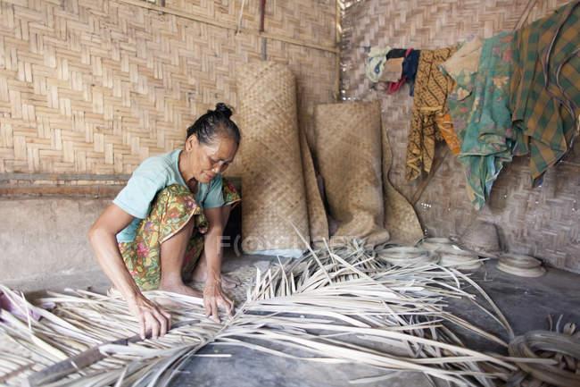 Indonésia, Lombok, mulher trabalhando em sua cabana — Fotografia de Stock