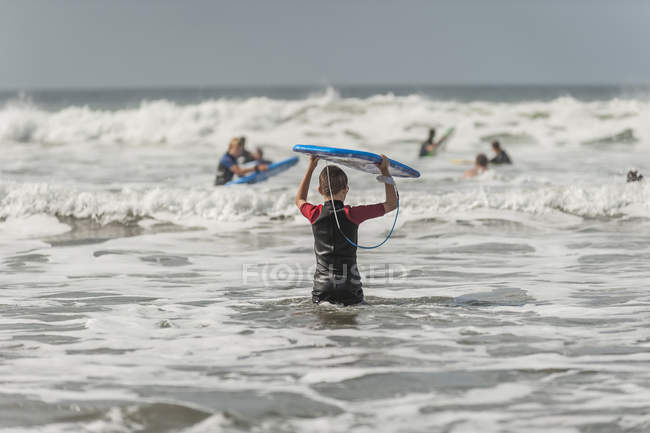 Boy carrying surfboard into the sea at daytime — Stock Photo