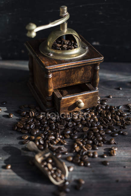Grinding coffee with vintage coffee mill on wood — Stock Photo