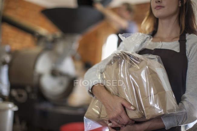 Woman holding coffee beans packed in paper bags — Stock Photo