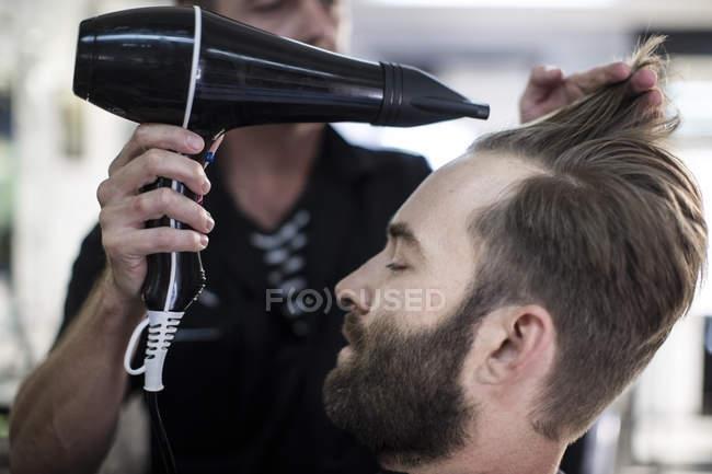Peluquería pelo secado por soplado de un cliente en la barbería - foto de stock