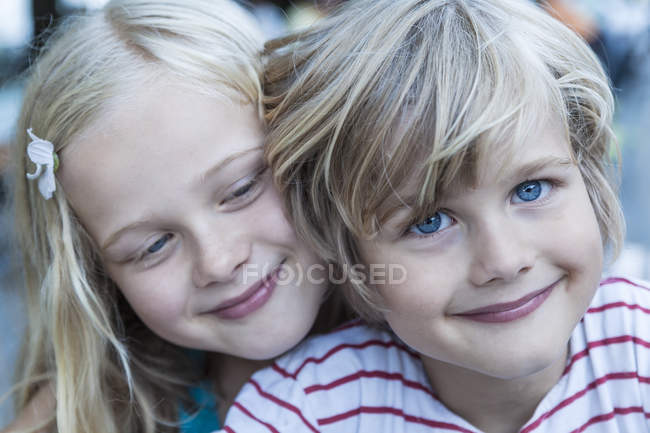 Portrait of smiling little boy and his sister head to head — Stock Photo