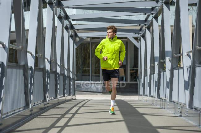 Молода людина, біг на мосту — стокове фото