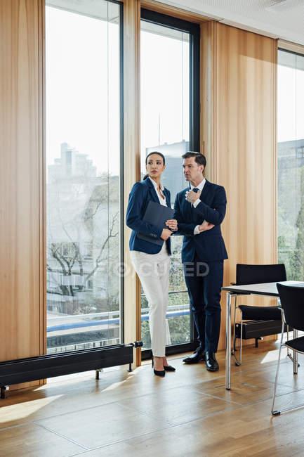 Бізнесмен і бізнес-леді в офісі розмови у вікні програми — стокове фото