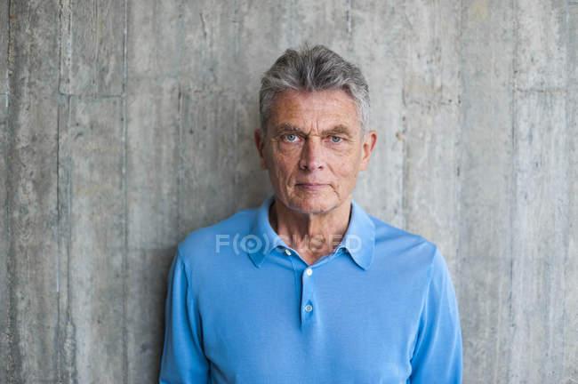 Porträt eines älteren Mannes an Betonwand — Stockfoto