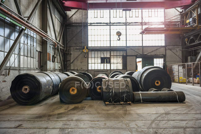 Rolls of rubber in factory hall, backlit — Stock Photo