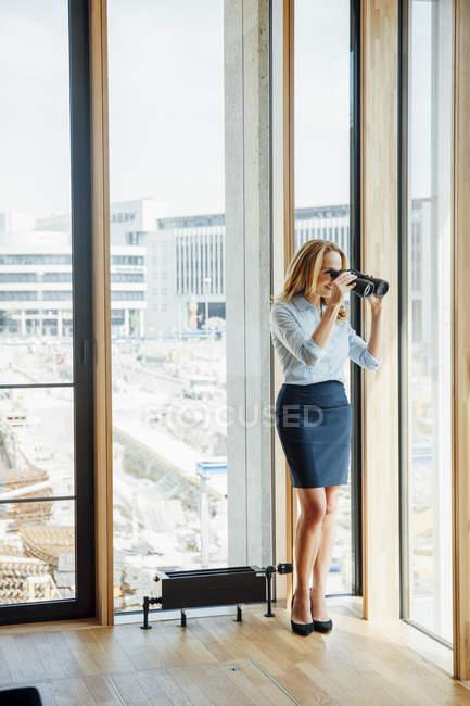 Donna d'affari con binocolo che guarda fuori dalla finestra — Foto stock