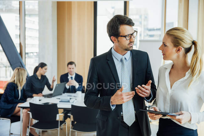 Businessman and businesswoman talking in office with meeting in background — Stock Photo