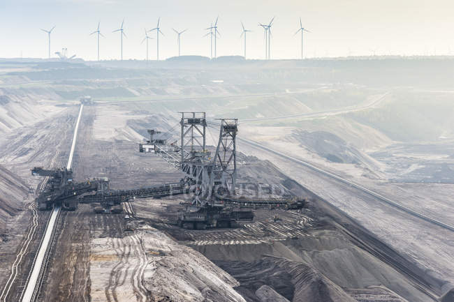 Germany, North Rhine-Westphalia, Grevenbroich, Garzweiler surface mine, Stacker and conveyor belt, wind wheels in the background — Stock Photo